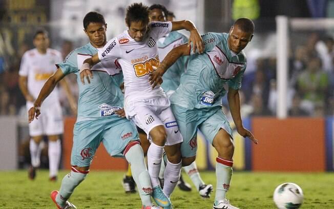 Neymar tenta passar no meio de dois  marcadores do Náutico