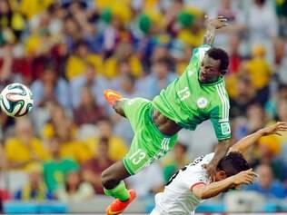 Juwon Oshaniwa, da Nigéria, disputa bola com vigor com Reza Ghoochannejhad, do Irã