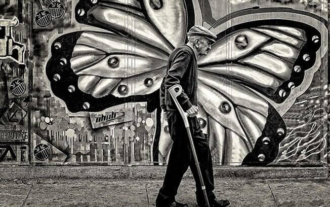 Um senhor caminhando com sua bengala