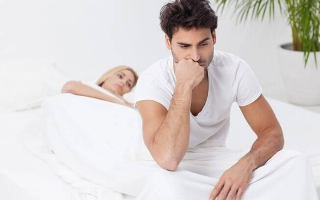 homem triste na cama com mulher ao fundo