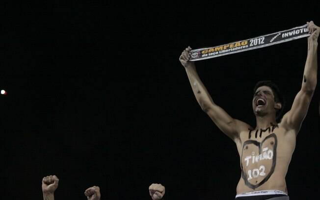 Pintado com as cores do Corinthians, torcedor  canta no Pacaembu antes da partida