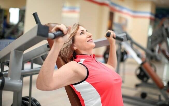 Mulher de meia idade treinando musculação na academia