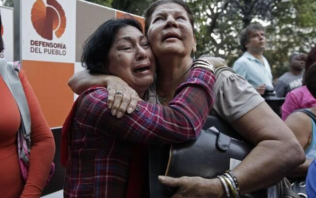 Mulheres choram e se abraçam após o anúncio da morte de Chávez pelo vice Nicolas Maduro (05/03)