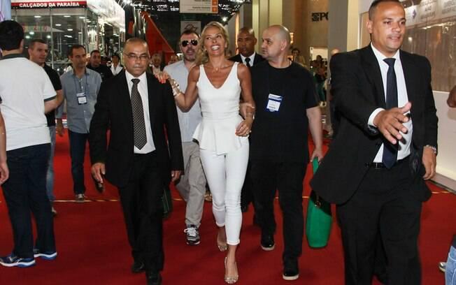 Adriane Galisteu faz pose para foto abraçada aos seguranças de feira de calçados