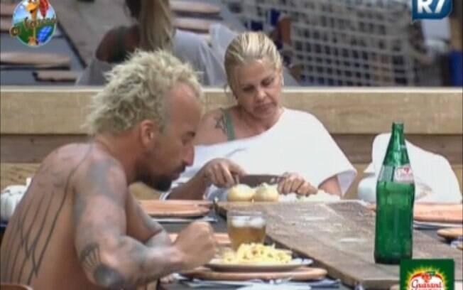 Monique corta cebola enquanto Gui almoça sozinho