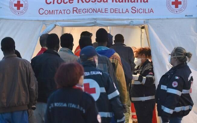 Migrantes oriundos da Líbia recebem atendimento de autoridades na Sicília, nesta quinta-feira