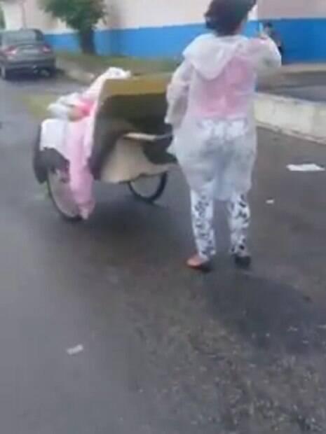 mulher carrega marido em carrinho de mão
