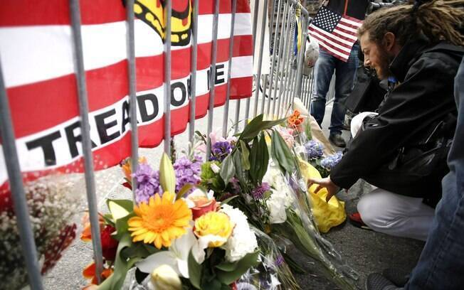 Homem coloca bilhete com flores em barricada de polícia perto da linha de chegada da Maratona de Boston (16/04). Foto: AP