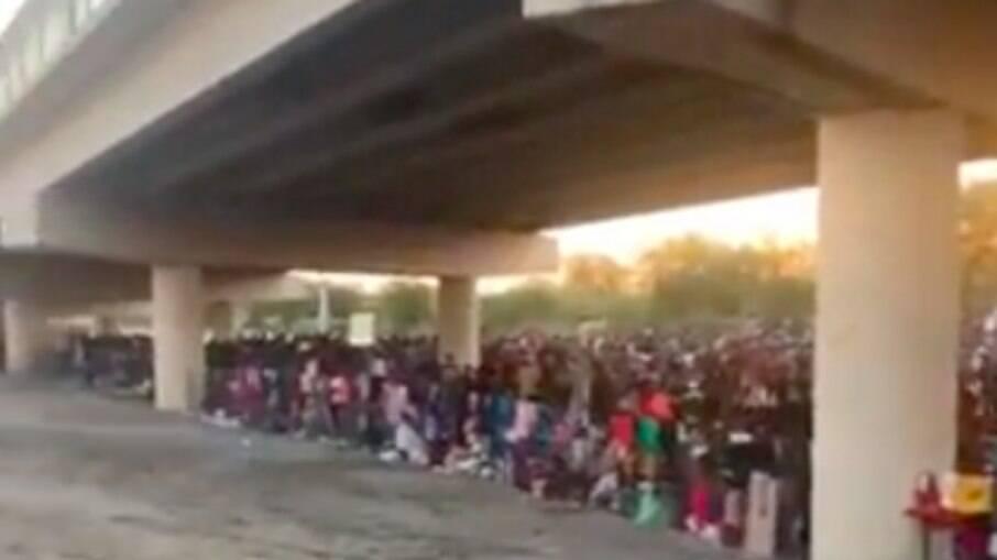 Imigrantes debaixo da Ponte Internacional Del Rio enquanto esperam para se entregar à Patrulha de Fronteira dos EUA e pedir asilo