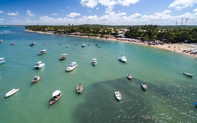 Os barcos de pesca dividem espaço com banhistas que procuram o que fazer na Praia do Forte durante o ano
