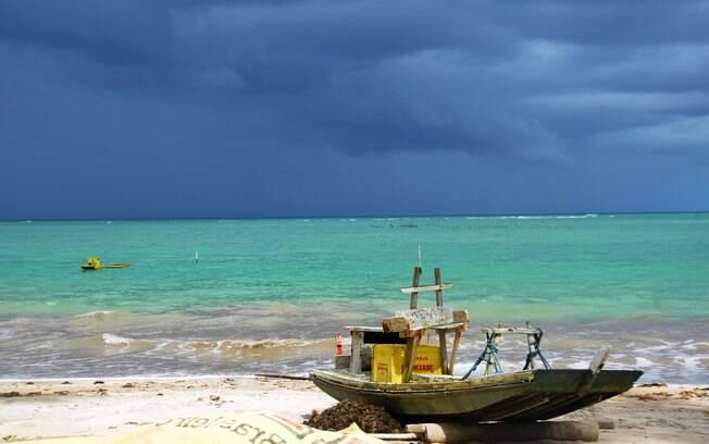 Praia com um barco na areia e mar azul claro.