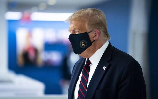 O presidente Donald Trump usa uma máscara enquanto visita a sede nacional da Cruz Vermelha americana em Washington