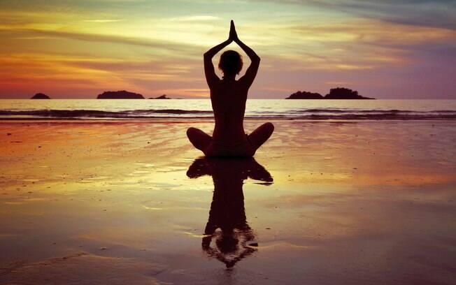 pessoa meditando em uma praia em frente ao pôr do sol