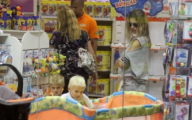 Fernanda Lima observa gêmeos brincando em loja
