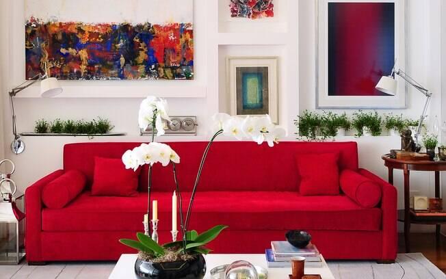 No contraponto ao sofá vermelho e os quadros coloridos, elementos brancos, como a mesa de centro em laca brilhante, a parede e o cinza claro do tapete