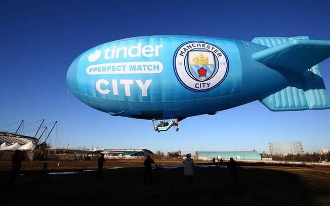 Pequeno dirigível foi erguido para iniciar a parceria entre o Manchester City e o aplicativo de paquera