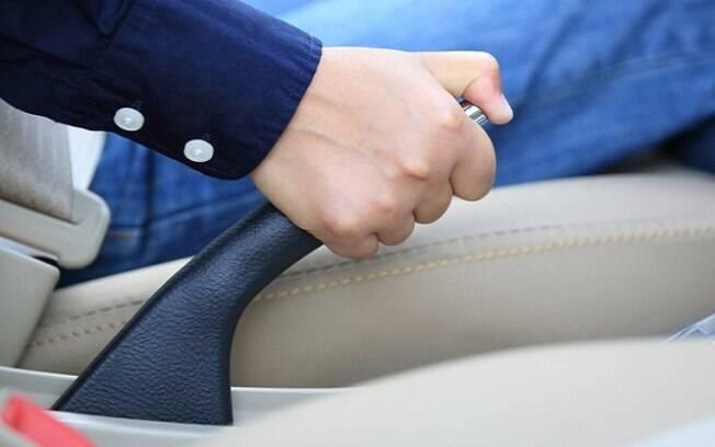Solte o freio de mão do carro parado, engate o câmbio na marcha ré e coloque um peso sobre o pedal da embreagem. Se for automático, deixe na posição P.