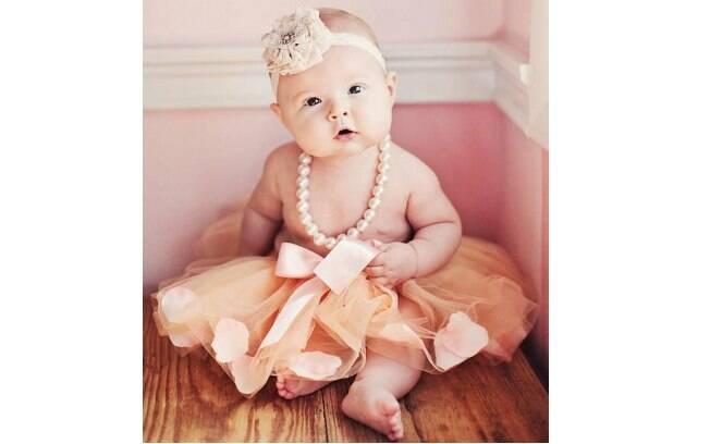 Entre outros itens, esta bebê usa uma faixa com uma grande flor. Foto