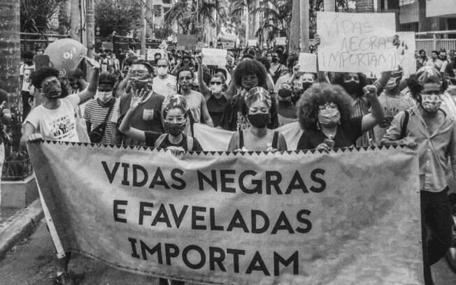 pessoas em manifestação com faixa escrito 'vidas negras e faveladas importam'