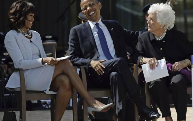 Obama ri sentado entre sua mulher e a ex-primeira-dama Barbara Bush na inauguração de Centro Presidencial George W. Bush (25/4/2013)