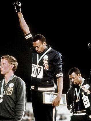 Tommie Smith (C) e John Carlos (e) fazem o gesto marcante das Olimpíadas de 1968, acompanhados pelo australiano Peter Norman: pódio dos 200m