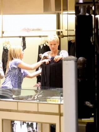 Xuxa pede a vendedora para ver peças de roupa
