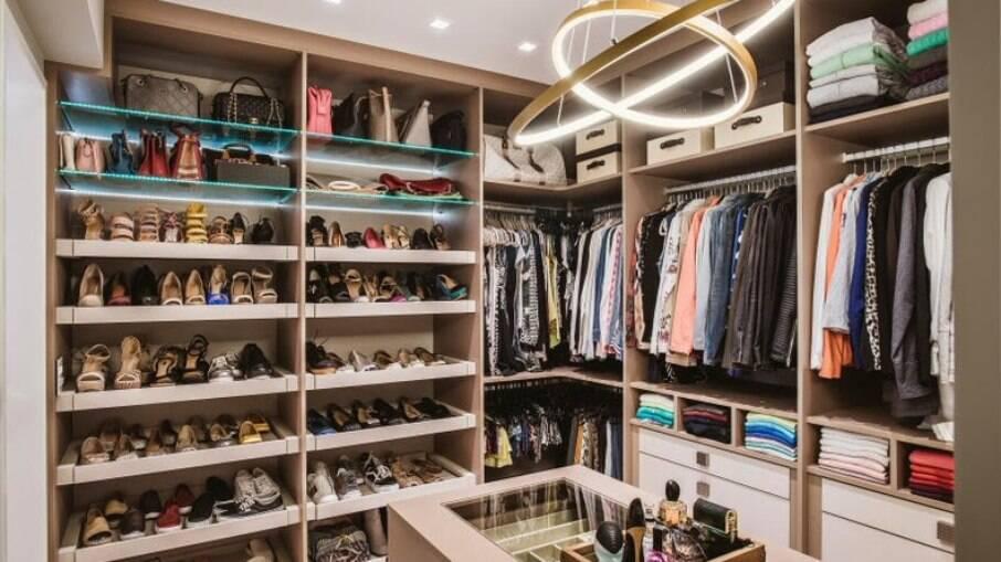Em um closet de casal,as profissionais dedicaram um espaço generoso para a disposição dos calçados e a coleção de bolsas