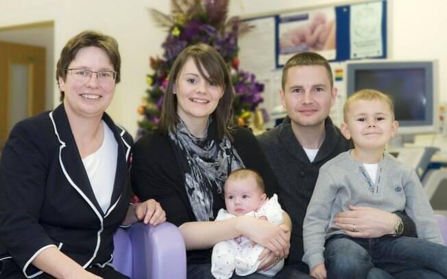 Donna com a filha Amelia no colo, ao lado do filho mais velho, do marido e da professora Siobhan Quenby