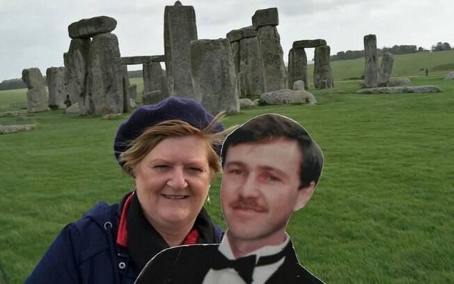Na foto, Michelle Bourke está em Stonehenge. Ela viaja pelo mundo e faz registros com um papelão do marido falecido