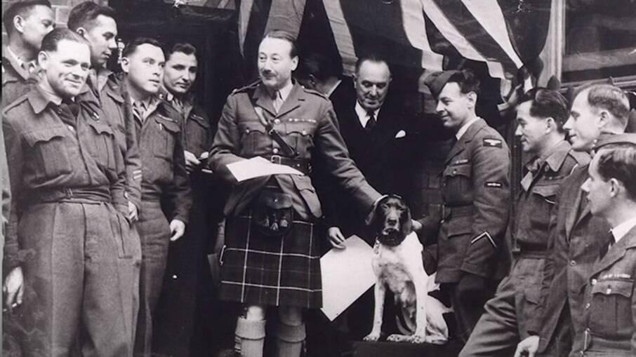 Judy ao lado de Frank e outros tripulantes da marinha britânica