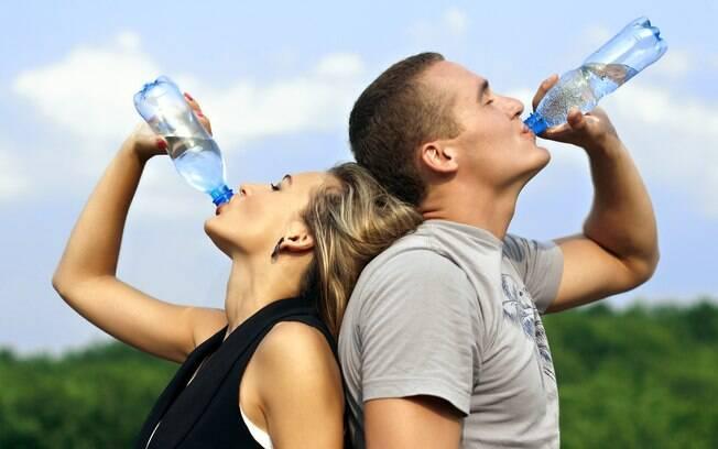 Casal tomando água após atividade física ao ar livre