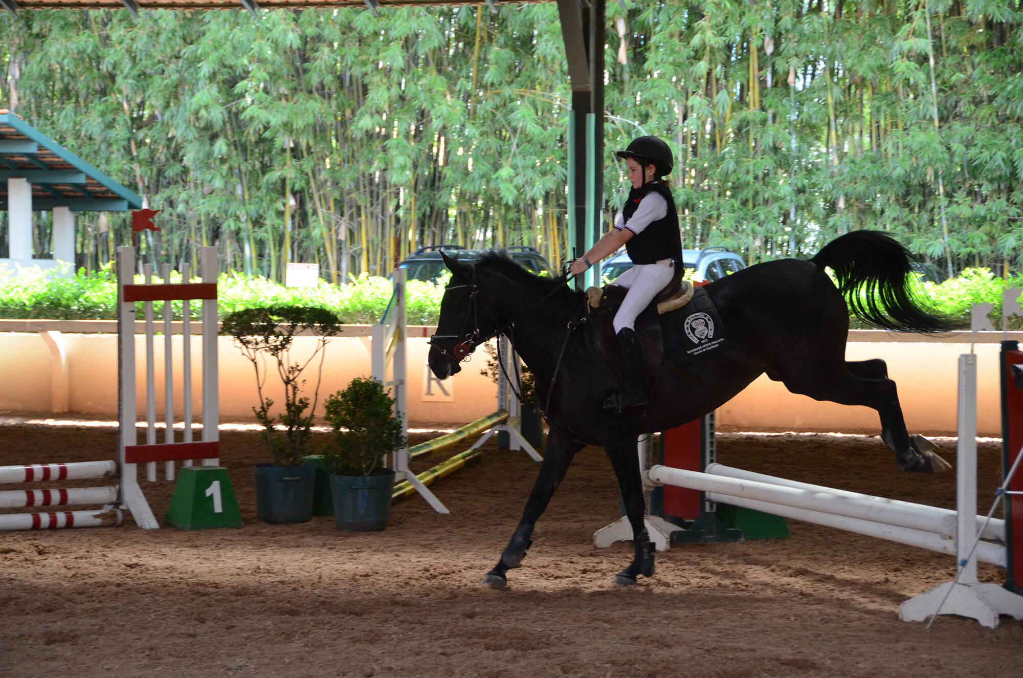 Criança participando de uma prova de salto no picadeiro coberto da escola de equitação da Sociedade Hípica Paulista. Foto: Divulgação/Hípica Paulista