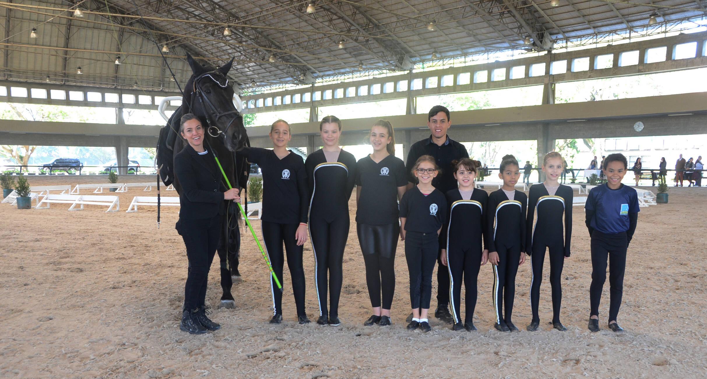 Crianças da escola de equitação da Hípica Paulista reunidas momentos de uma apresentação no picadeiro coberto do clube. Foto: Divulgação