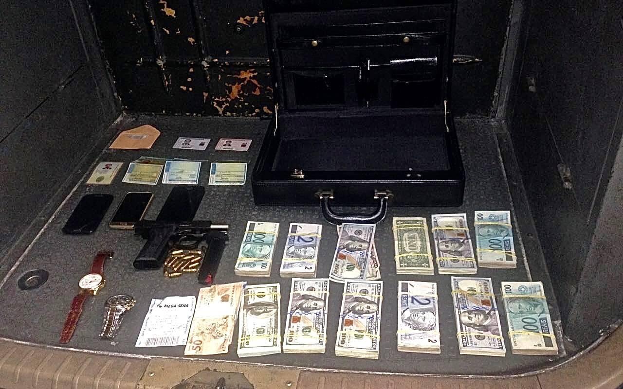 11 mil dólares, celulares, pistola e munição, documentos, relógios e o bilhete falso da Mega-Sena. Foto: PM Divulgação