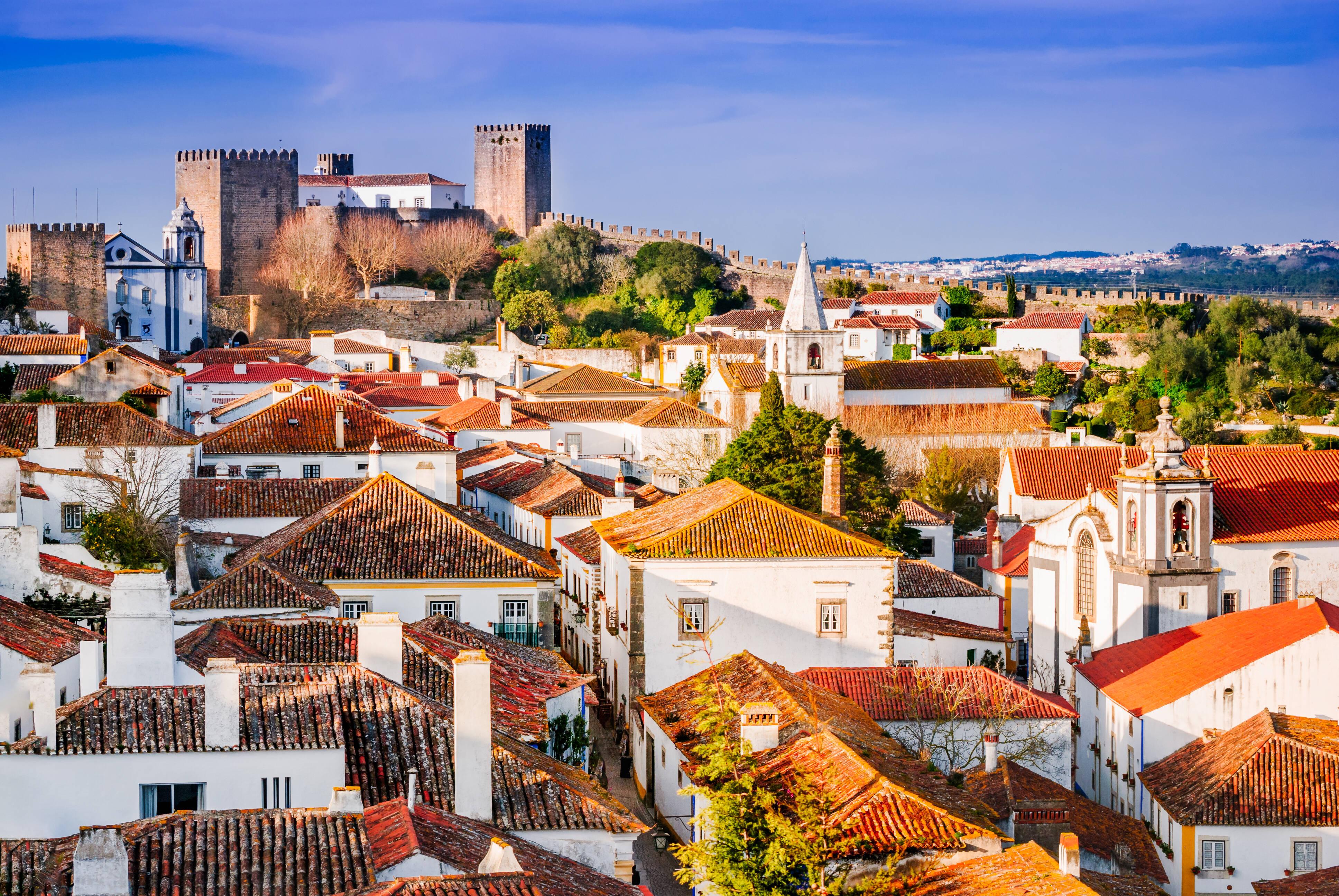 Óbidos é famosa por suas casas de paredes brancas e ruas sinuosas que cortam a cidade cercada por uma muralha. Foto: shutterstock