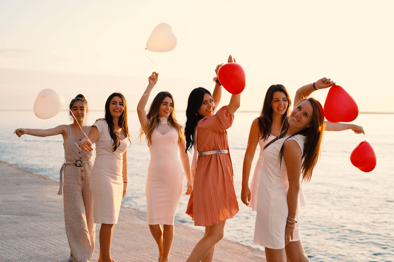Madrinhas com vestidos curtos para um casamento na praia, ao pôr do sol. Foto: Reprodução/Unsplash