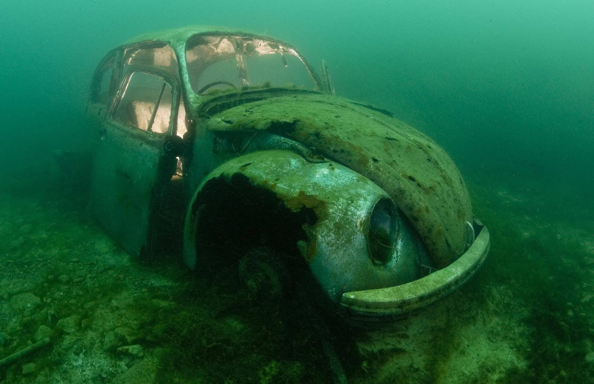 O fotógrafo Alex Mustard viaja o mundo atrás de imagens de embarcações e objetos afundados, como este Fusca deixado de propósito no fundo de um lago. Foto: Alexander Mustard/Solent News