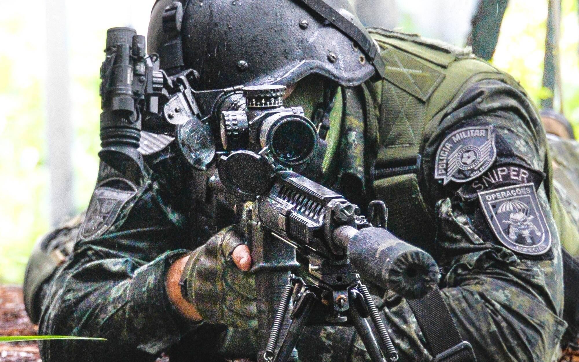 Atirador de Elite do COE observando uma área de interesse através da potente luneta do seu rifle. Note o equipamento de visão noturna sobre seu capacete. Foto: Major PM Luis Augusto Pacheco Ambar