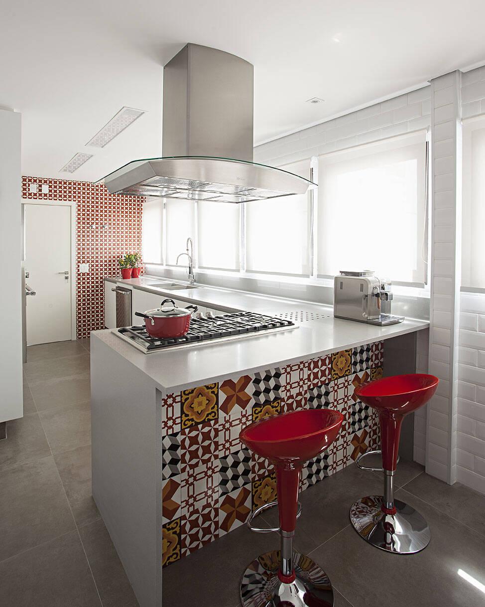 De cor branca, essa bancada de cozinha harmoniza com os bancos vermelhos e a estampa colorida. Foto: Divulgação/KORMAN Arquitetos