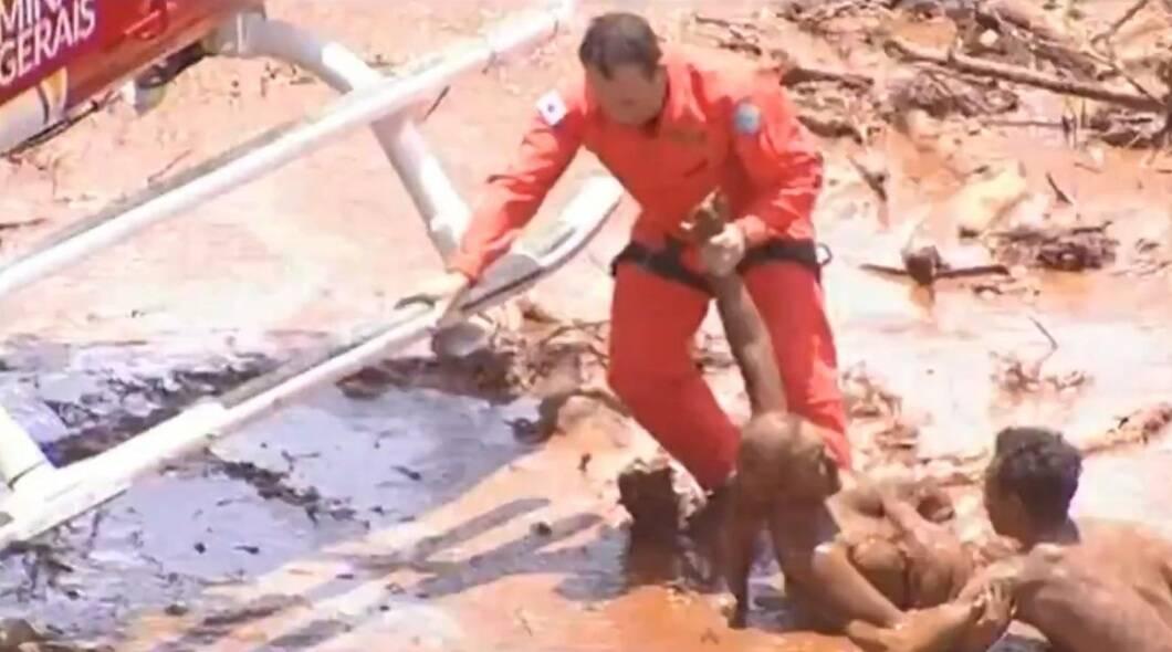 O helicóptero do Corpo de Bombeiros ficou a menos de um metro do chão, que estava totalmente tomado pela pelos rejeitos, e um agente desceu para tirar uma das vítimas do meio da lama. . Foto: Reprodução/Record TV