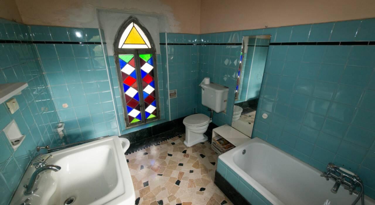 Um dos banheiros, que é azul turquesa e tem um vitral colorido, é um cômodo que aparece bastante no filme. Foto: Reprodução/House & Loft
