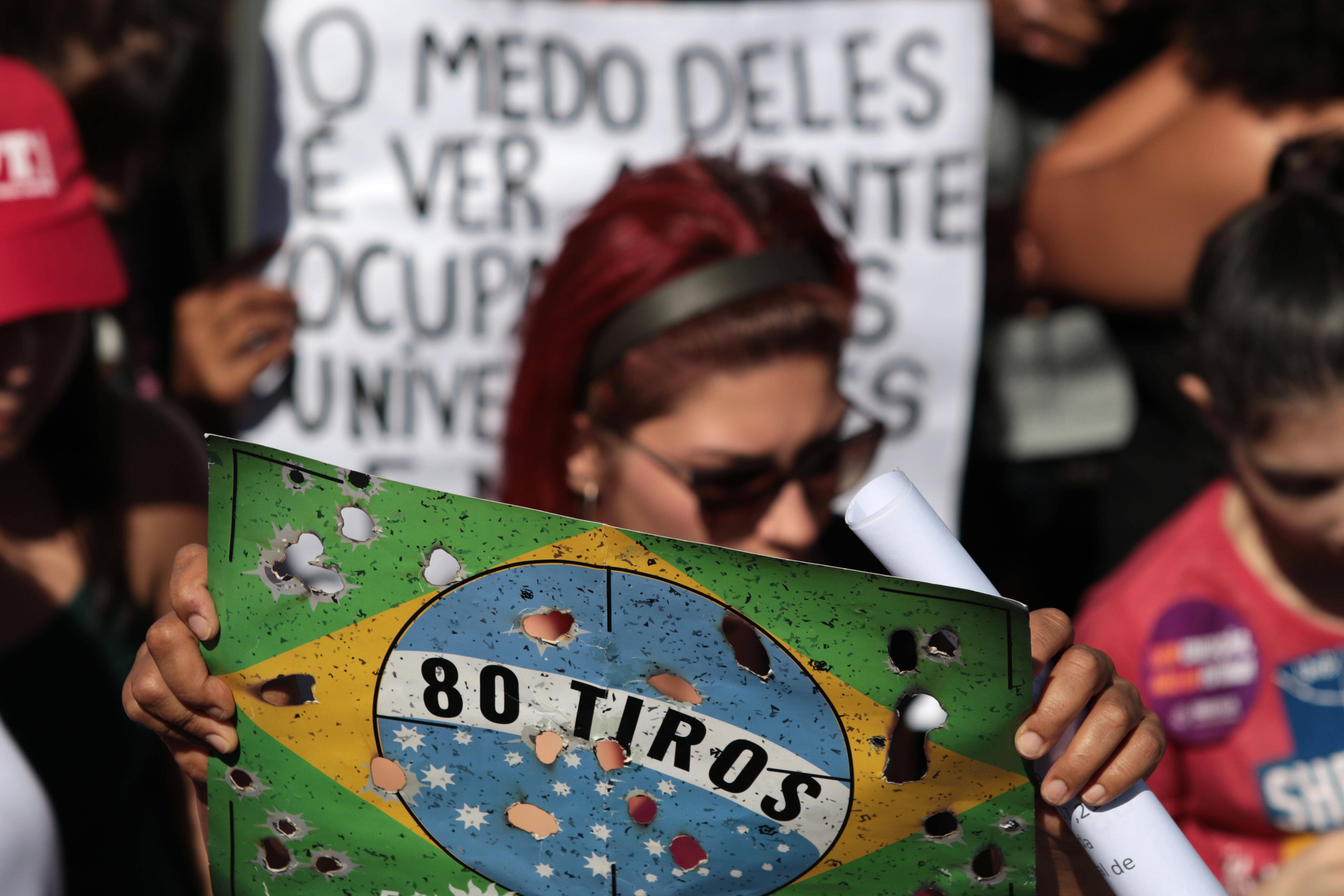 Em Brasília, manifestante levou cartaz lembrando morte de músico e de catador em ação do Exército no Rio de Janeiro. Foto: Claudio Reis/FramePhoto/Agência O Globo - 30.5.19