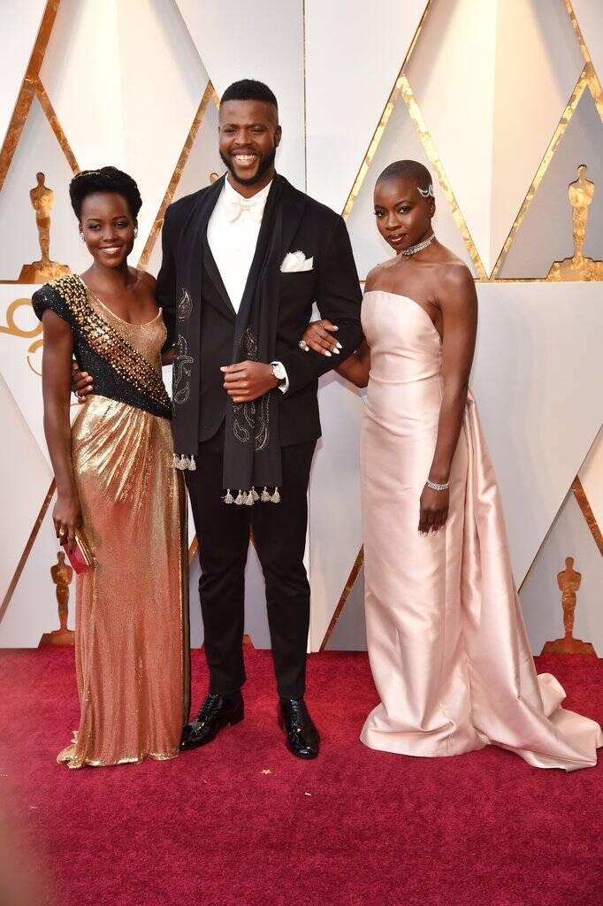 """Que tiro foi esse? Elenco de """"Pantera Negra"""" esteve presente no tapete vermelho do Oscar 2018 no último domingo (04). Lupita Nyong'o, Winston Duke e Danai Gurira arrasaram no close. Foto: Kevin Mazur/WireImage"""