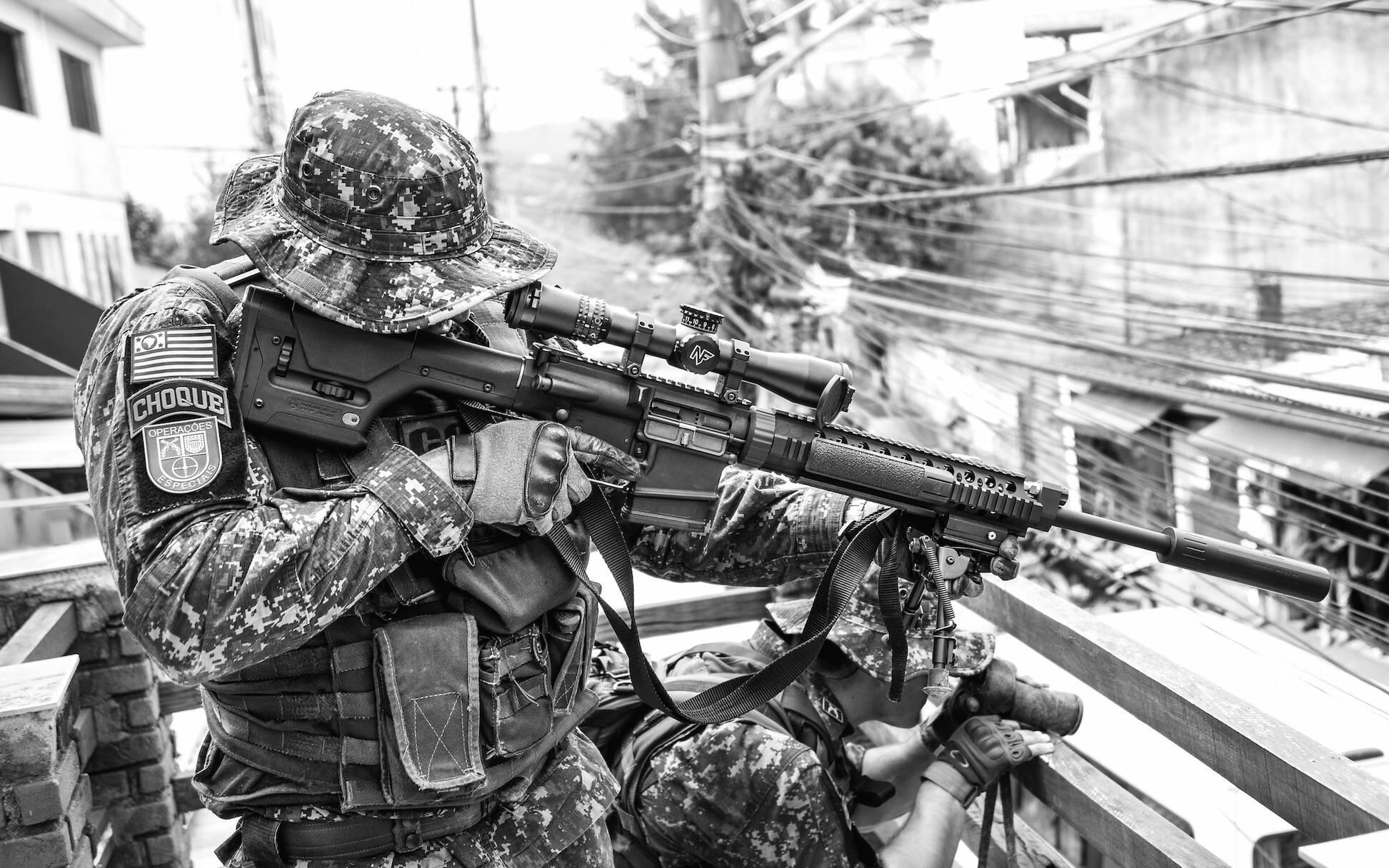 Posicionamento tático clássico: o Operador agachado usa um potente binóculo para localizar rapidamente possíveis ameaças para a equipe de solo que estão em deslocamento, e passar as informações precisas para o Atirador de Elite  . Foto: Major PM Luis Augusto Pacheco Ambar
