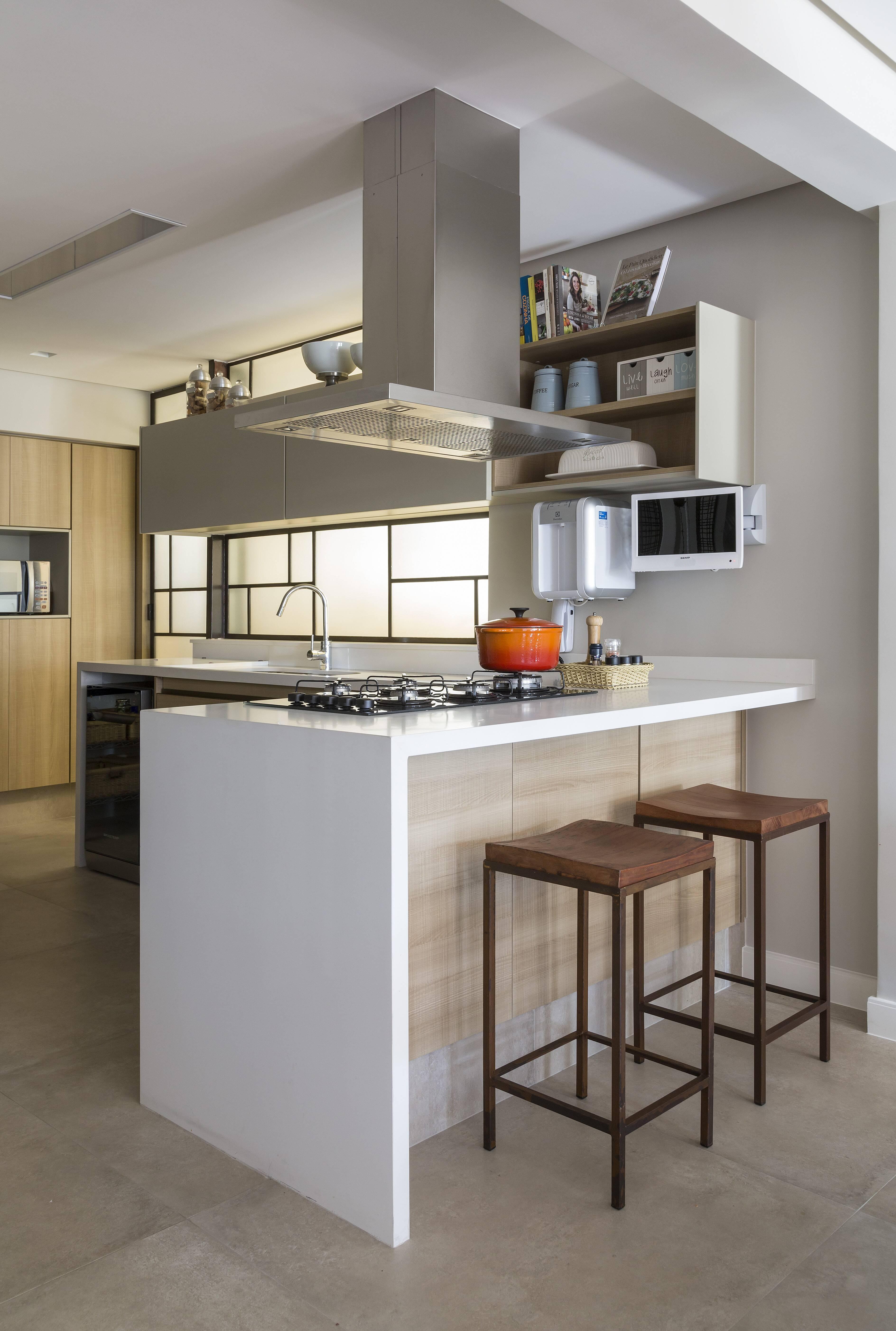 A bancada de cozinha é de quartzo, combinando com o branco dos gabinetes e em harmonia com a madeira clara.. Foto: Ana Yoshida Arquitetura e Interiores/Evelyn Müller