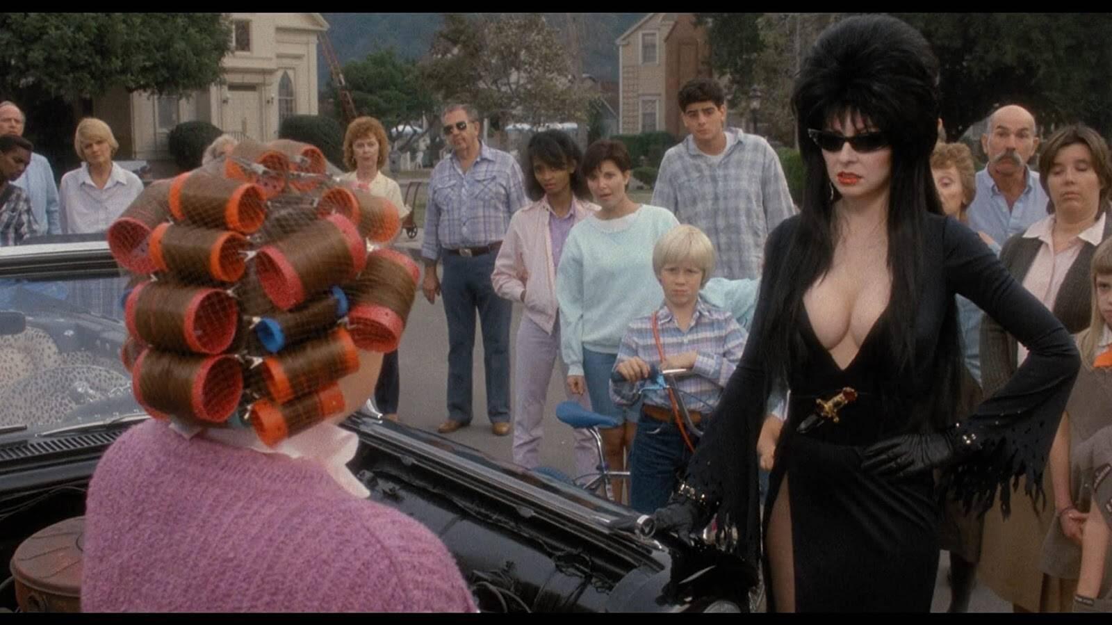 Em filme de horror cômico de 1988, Elvira chega a uma cidade conservadora de vestido preto, mega decote e maquiagem carregada. Foto: Reprodução
