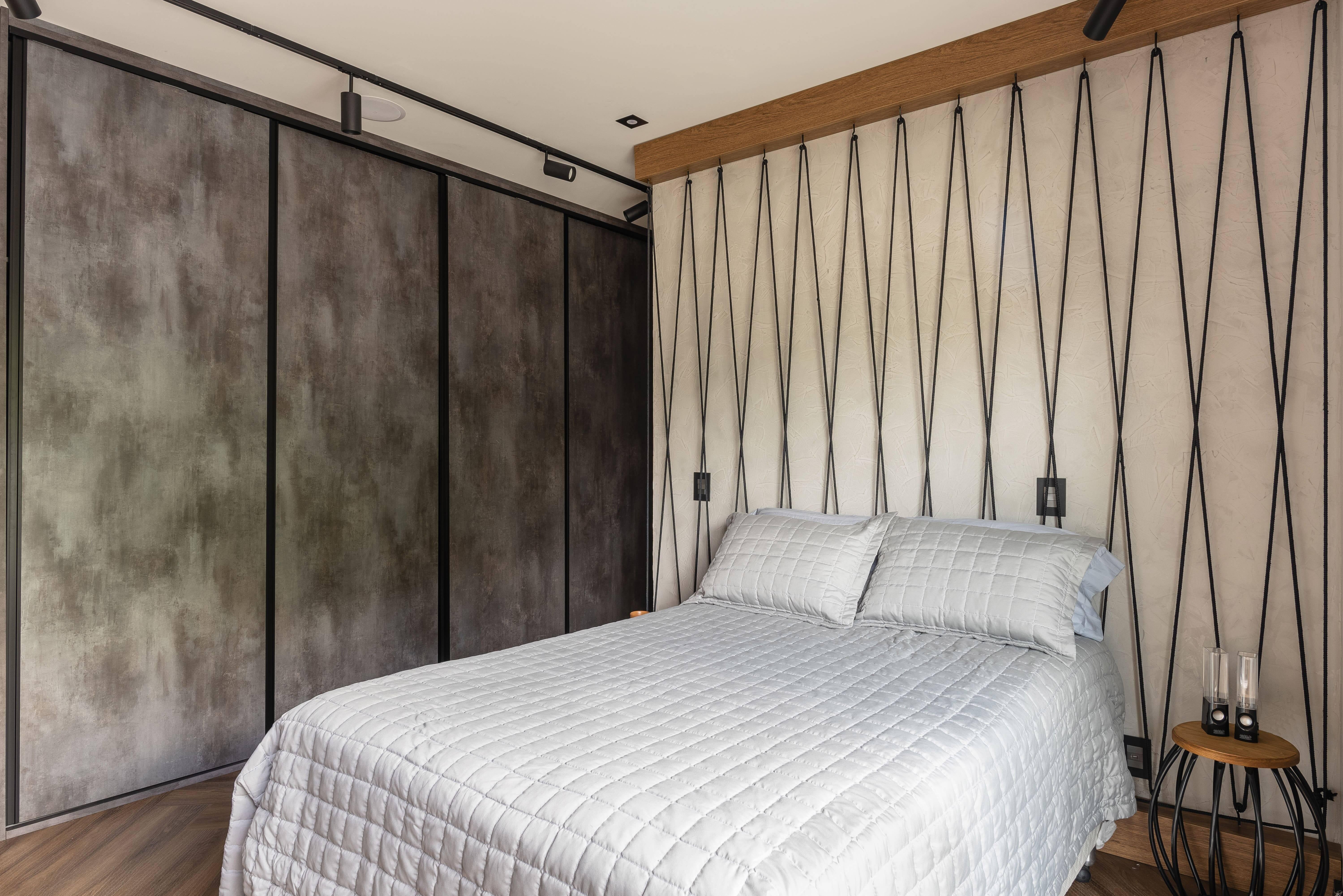 O painel ripado substitui a cabeceira da cama e se alinha ao estilo de decoração do quarto. Foto: Henrique Ribeiro