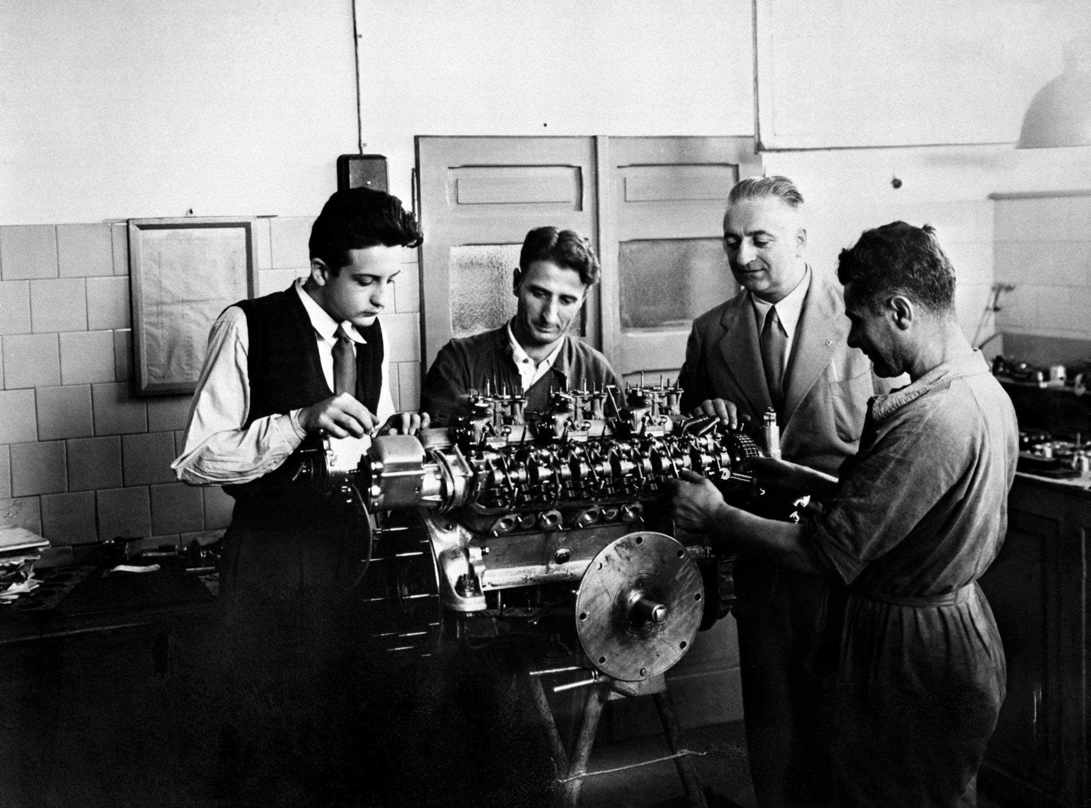 Enzo Ferrari ( o terceiro, no sentido horário) supervisiona a montagem de um motor. Foto: Divulgação