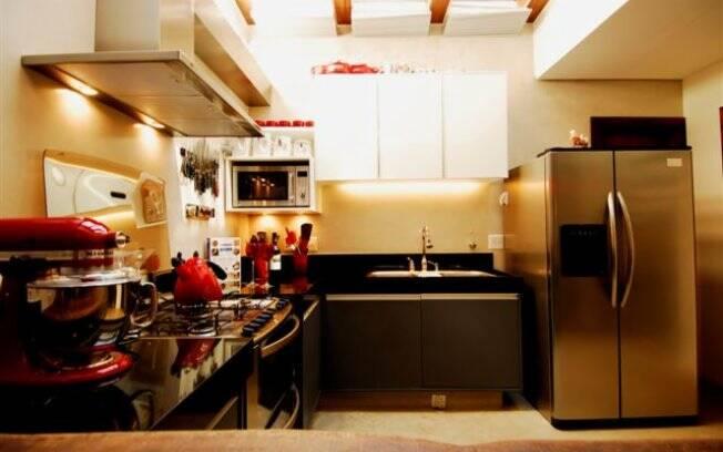 Cores sóbreas convivem em harmonia com tonalidades vibrantes. Exemplos disso são as luminárias vermelhas da cozinha