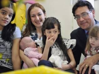 Carla com Marcela e Rafaela no colo, ao lado do marido e das outras filhas: sonho de ter 4 crianças